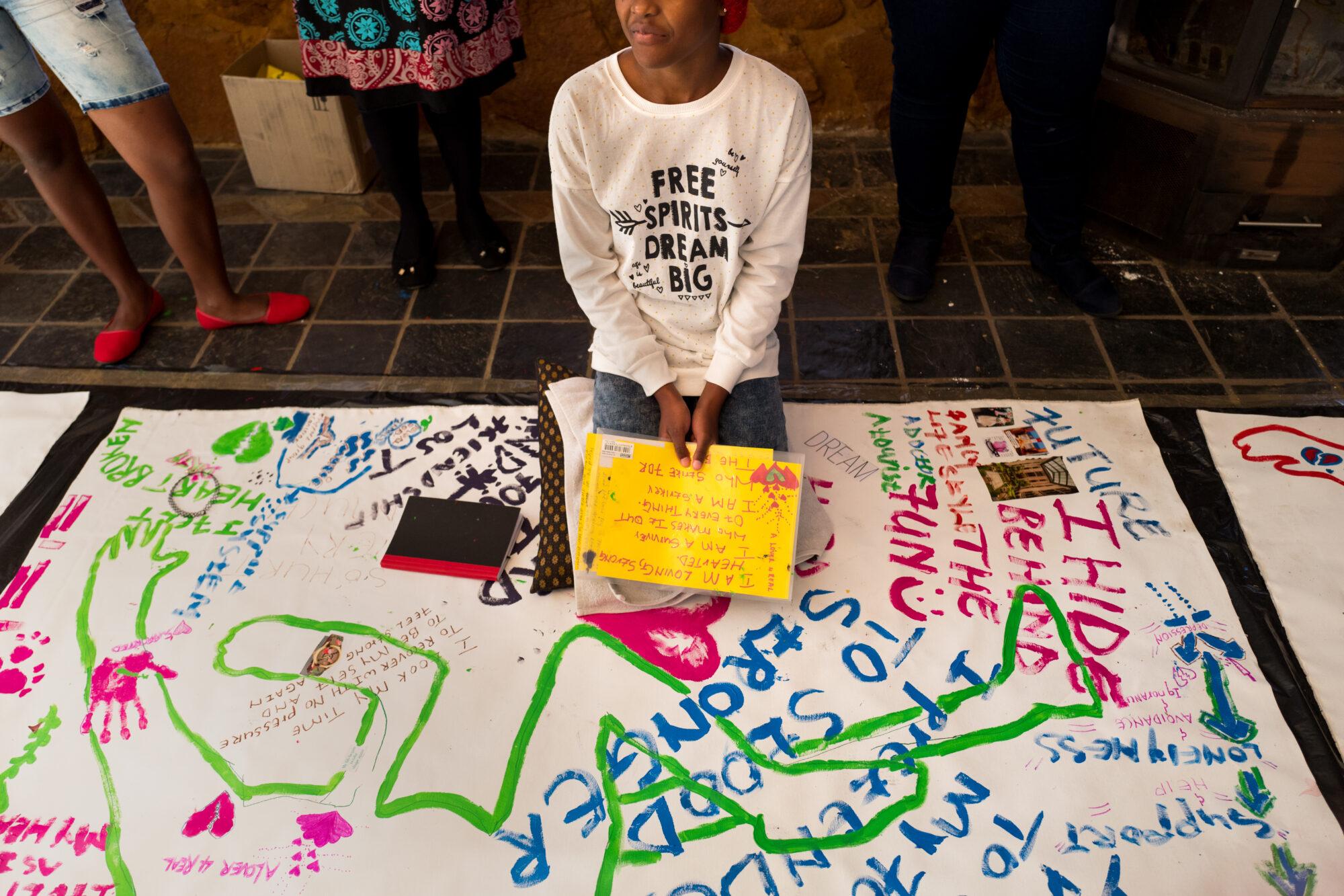 """Seksuaalisesta väkivallasta selviytynyt tyttö istuu lattialla """"Body Mapping"""" -kurssilla täyteen piirtämänsä suuren kankaan päällä."""