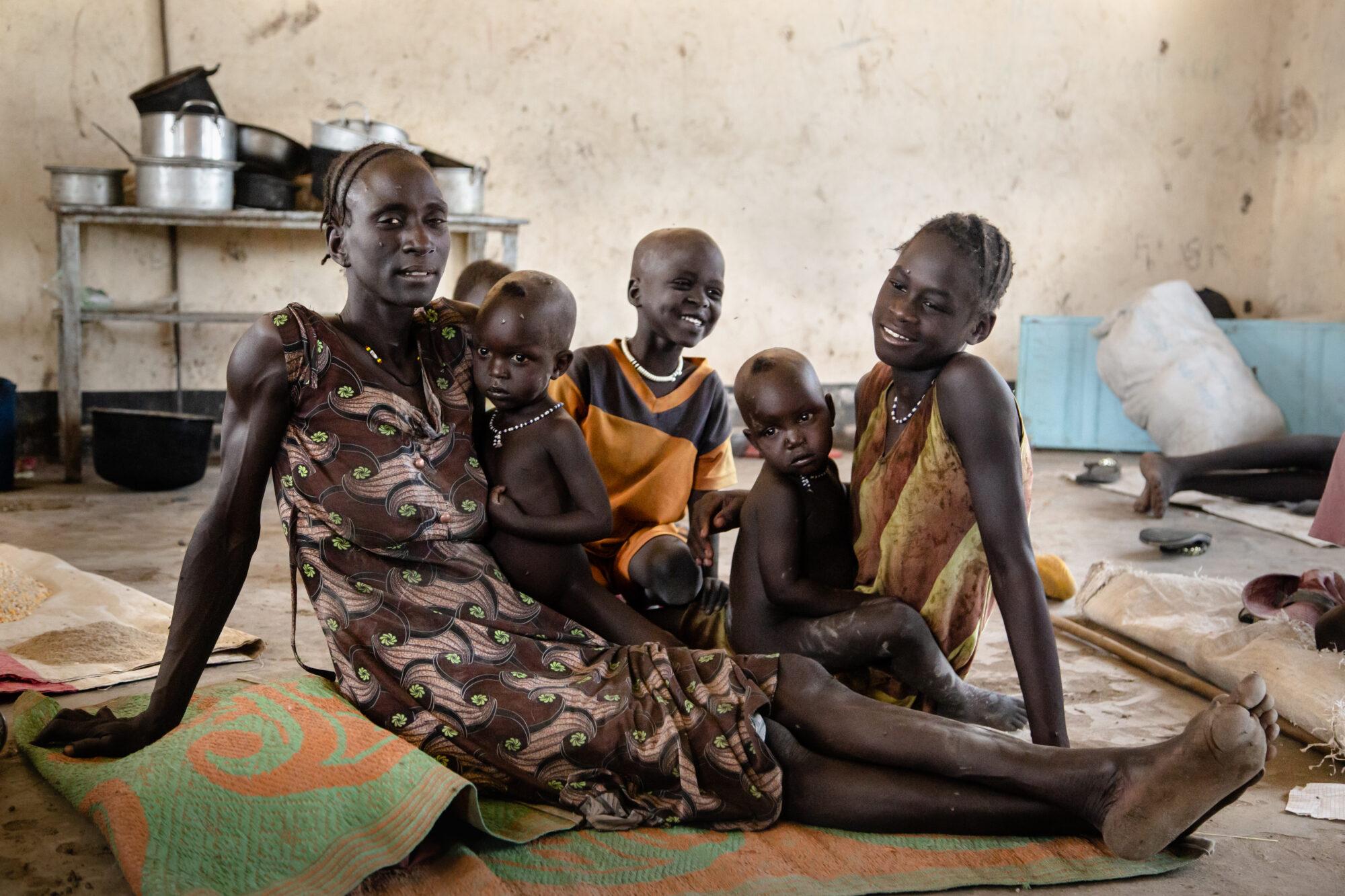 Viisihenkinen pakolaisperhe istuu lattialla hätämajoituksessa koulussa.