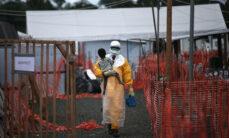 Työntekijä kantaa suojapuvussa ebolanhoitokeskuksessa lasta, jolla epäillään olevan ebola.
