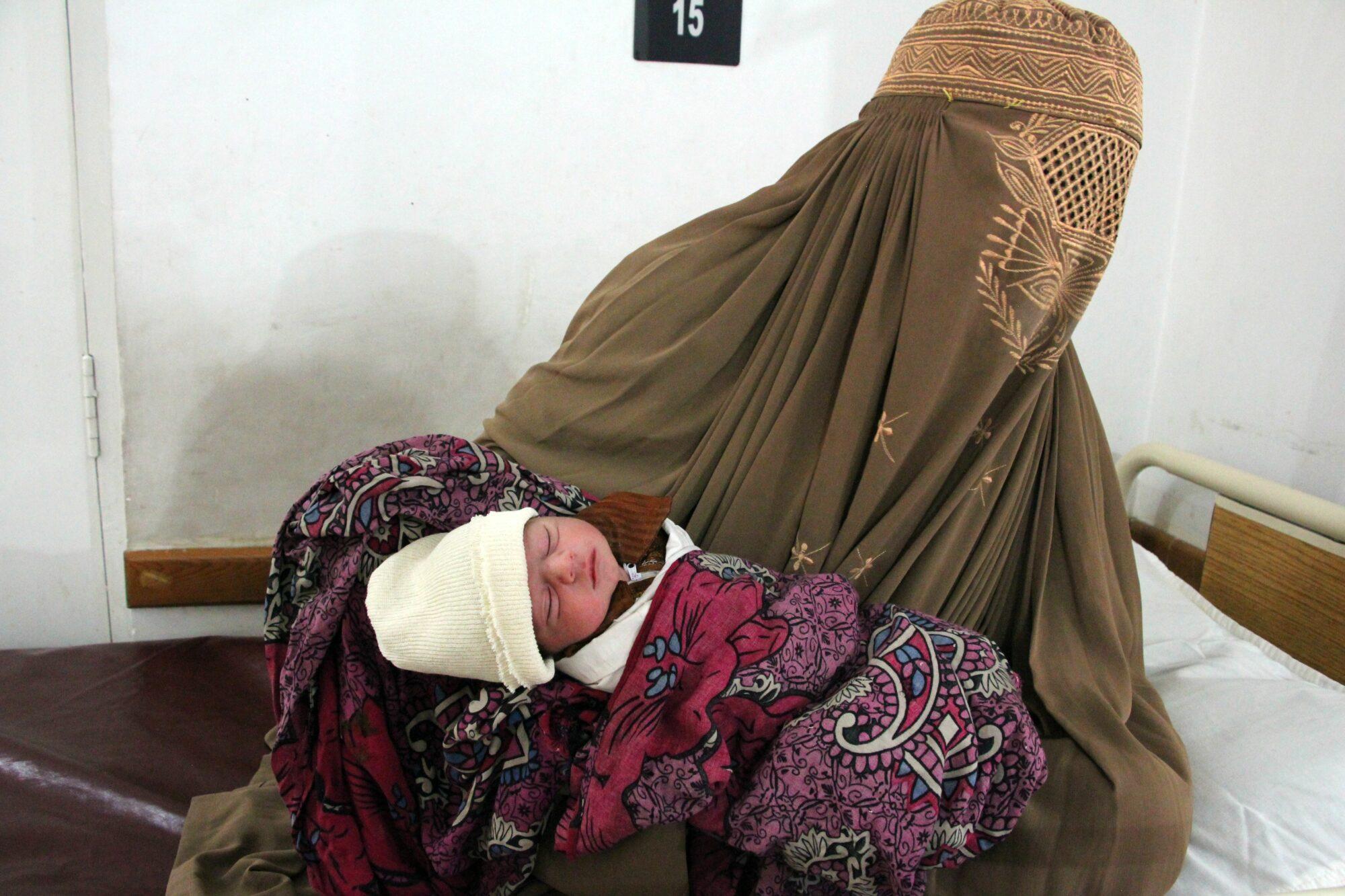 Nainen pitää sylissään vastasyntynyttä lastaan.