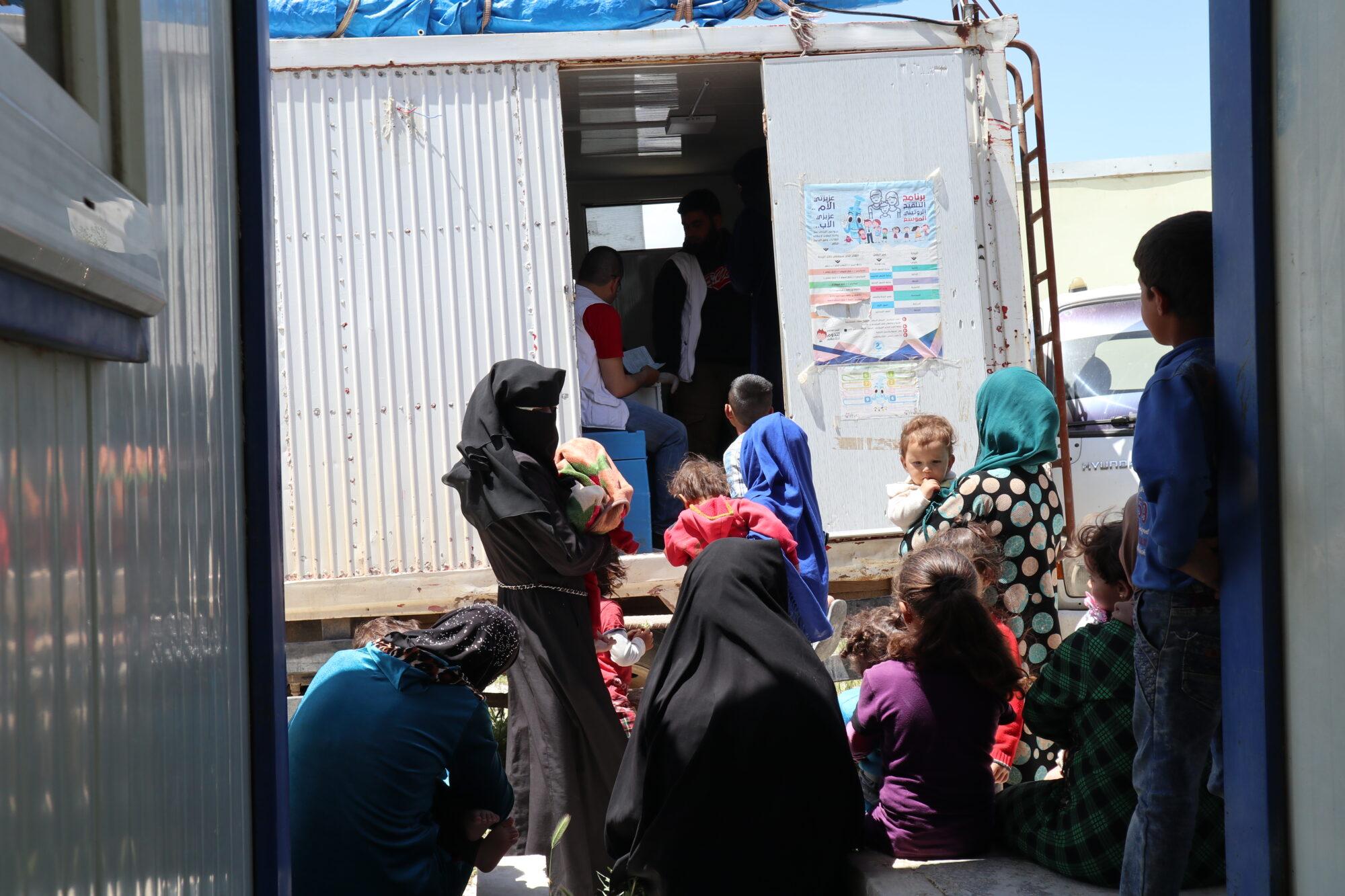 Naiset jonottavat lastensa kanssa mobiiliklinikan edessä.