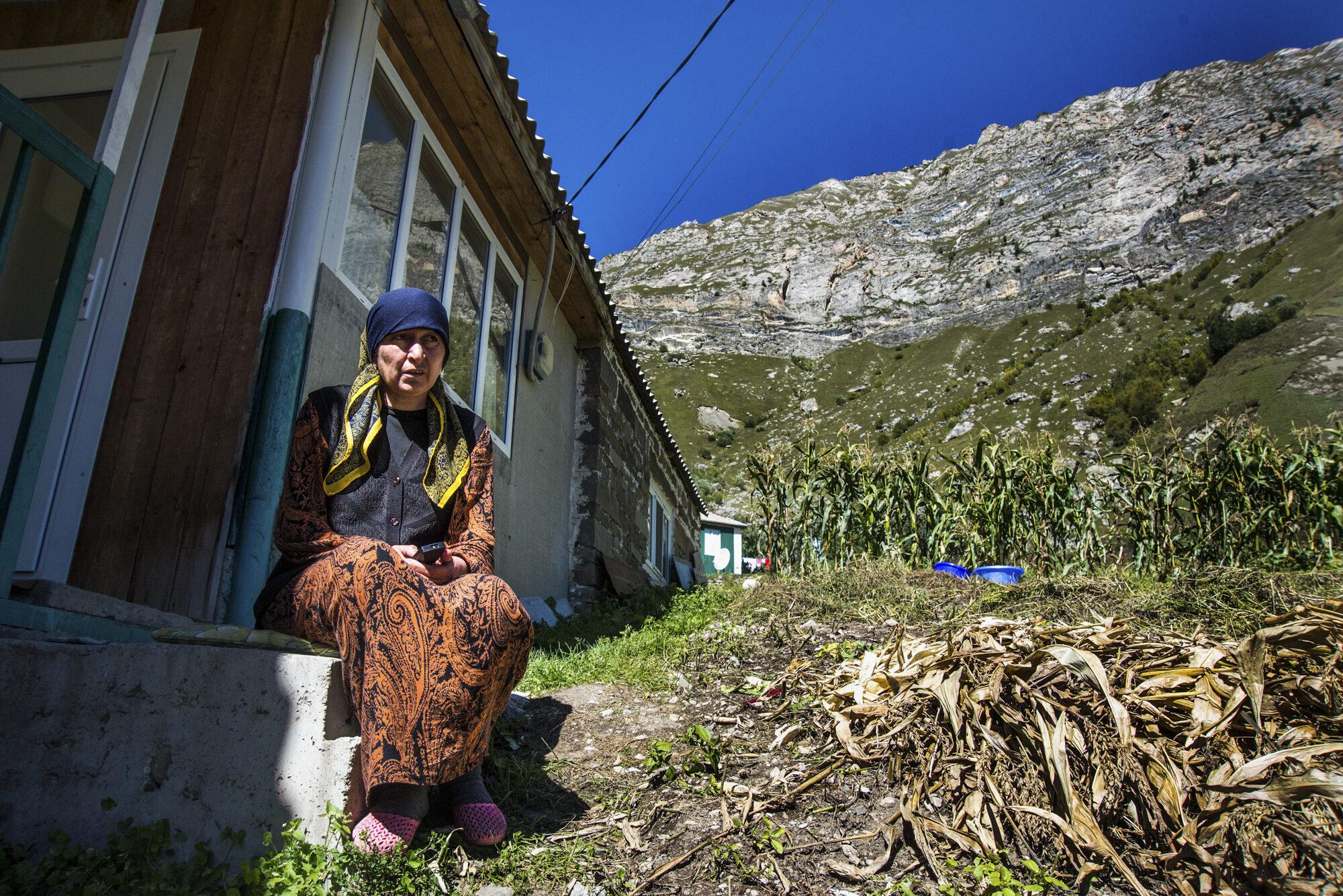 Nainen istuu kotinsa edessä vuoristossa.