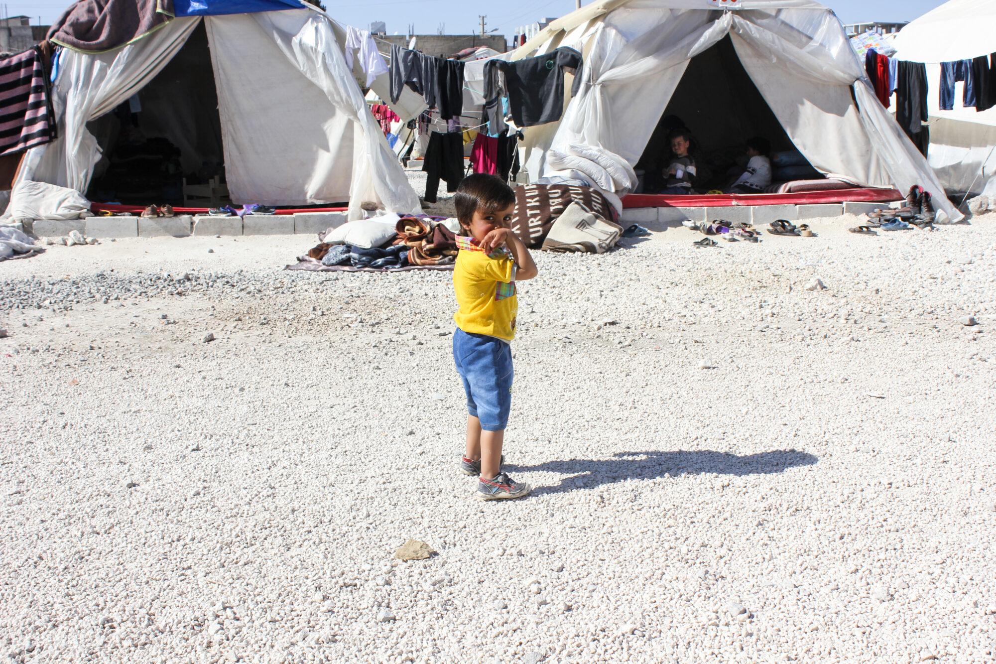 Syyrialaispoika seisoo tiellä paljain jaloin pakolaisleirillä.