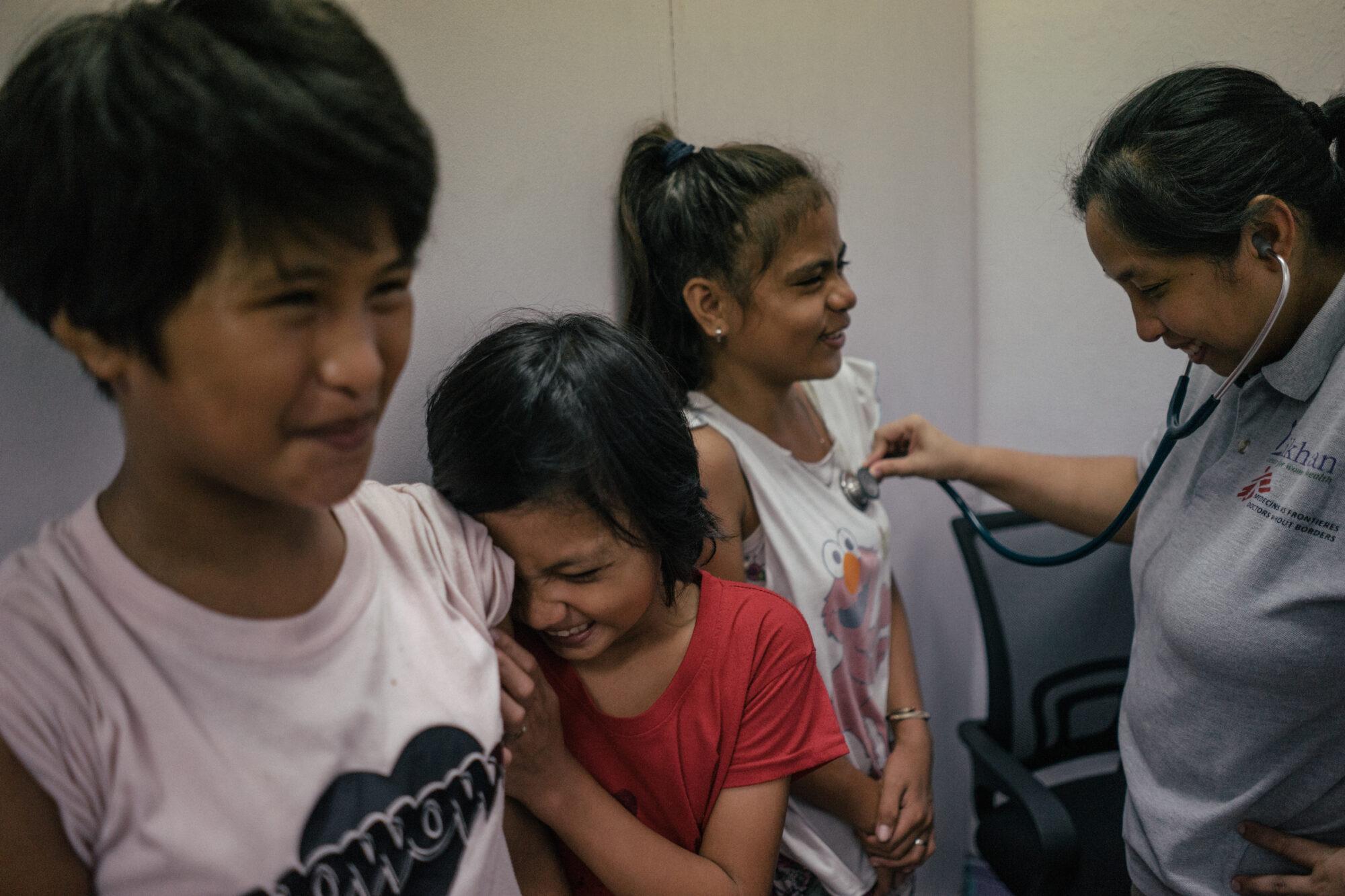 Tytöt nauravat odottaessaan pääsyä hpv-rokotukseen. Yhden rintaa kuunnellaan stetoskoopilla.