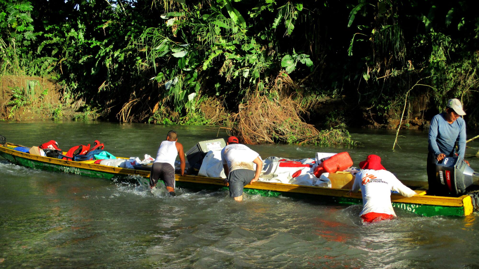 Järjestömme työntekijät kahlaavat matalikossa ja työntävät venettä, joka on täynnä tarvikkeita.