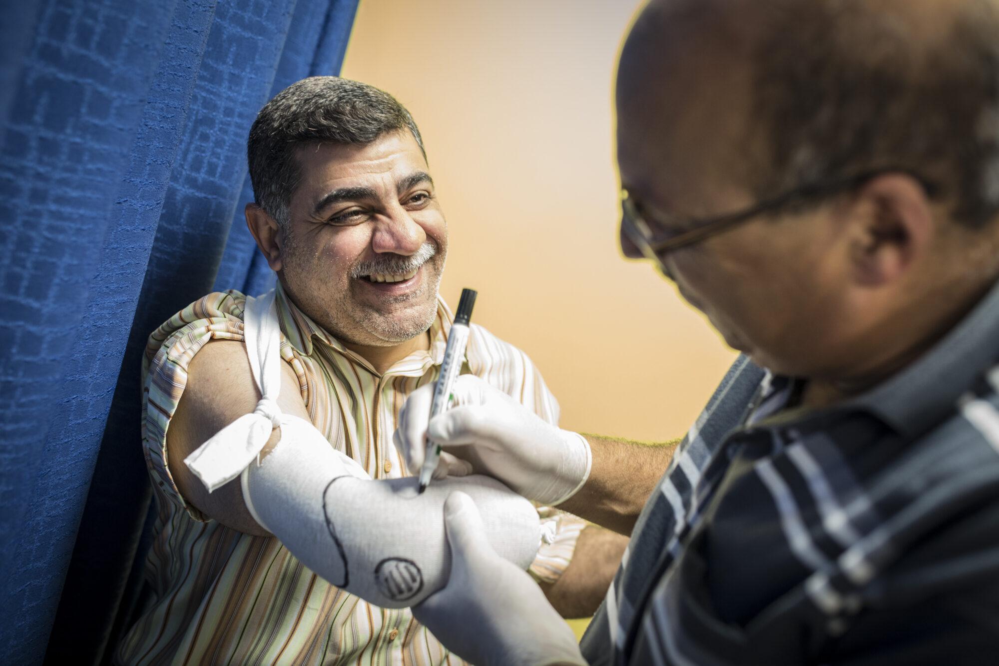 Irakilainen Haidar hymyilee leveästi saadessaan hoitoa oikean käden vammaan, joka aiheutui autopommista.