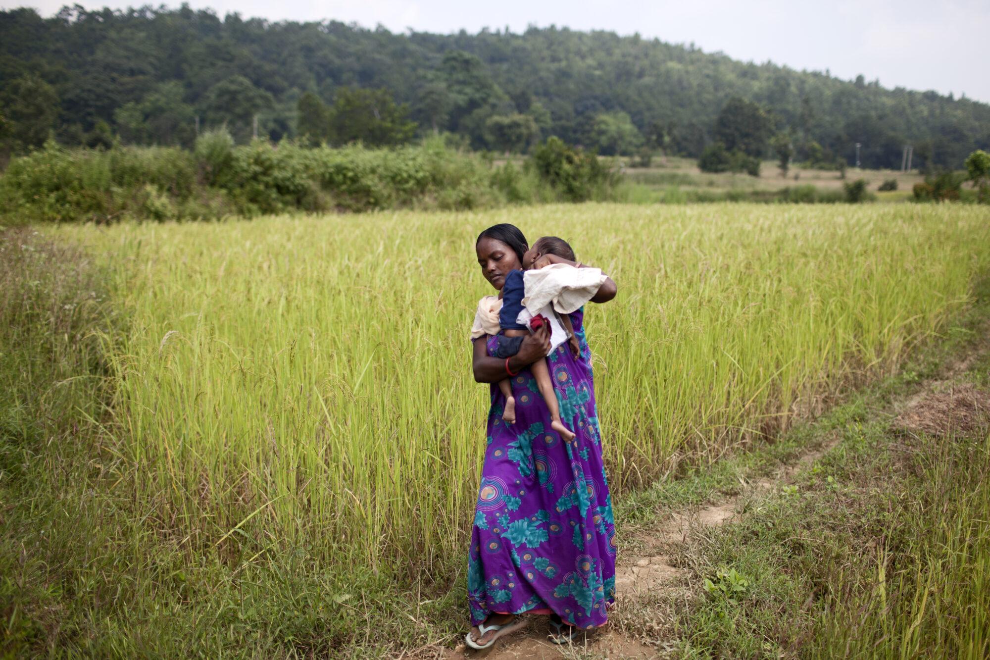 Äiti kantaa aliravitsemuksesta kärsivää vauvaansa pellon poikki terveysasemalle.
