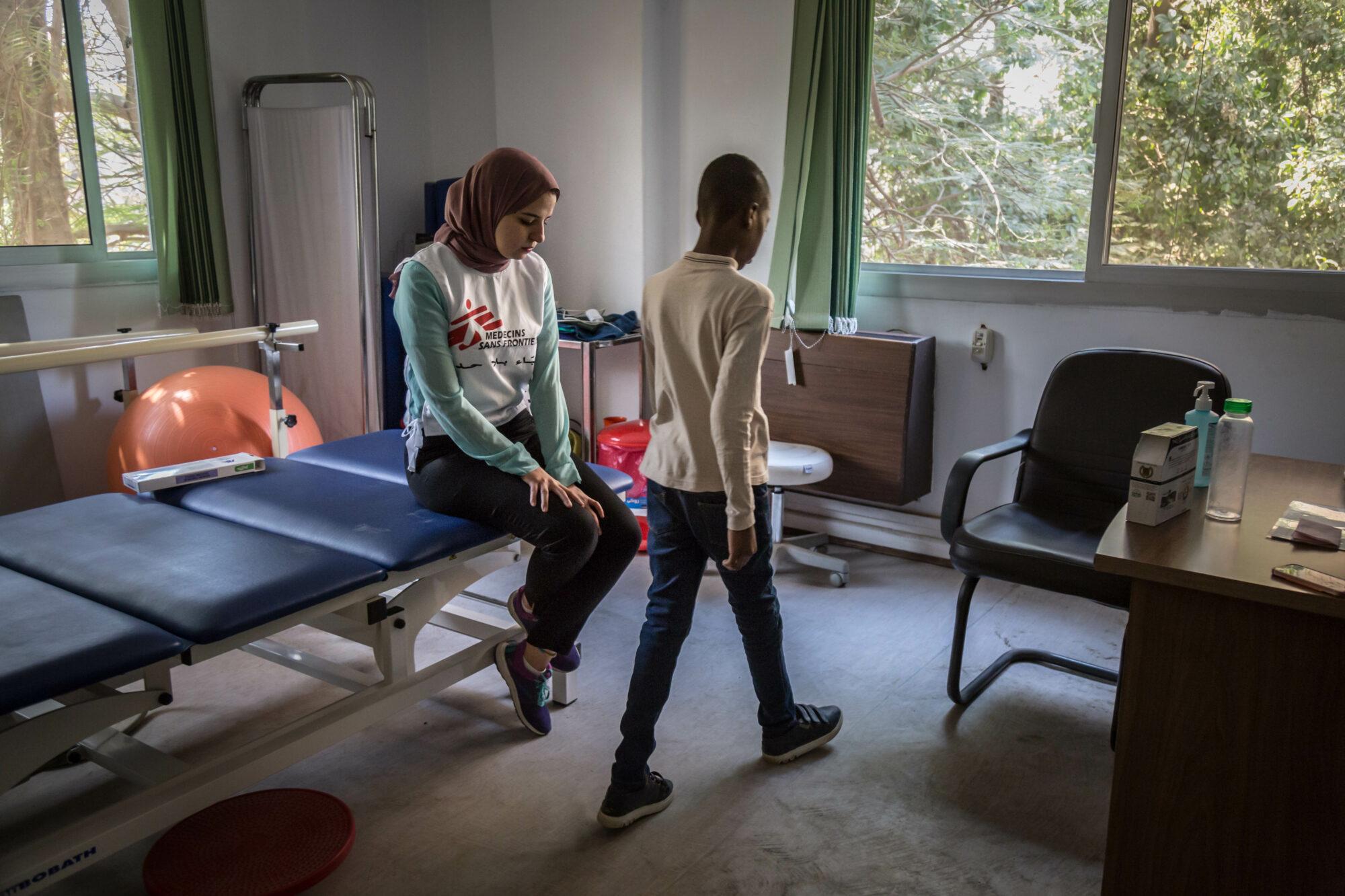 Fysioterapeutti seuraa pojan kävelyä vastaanotolla.