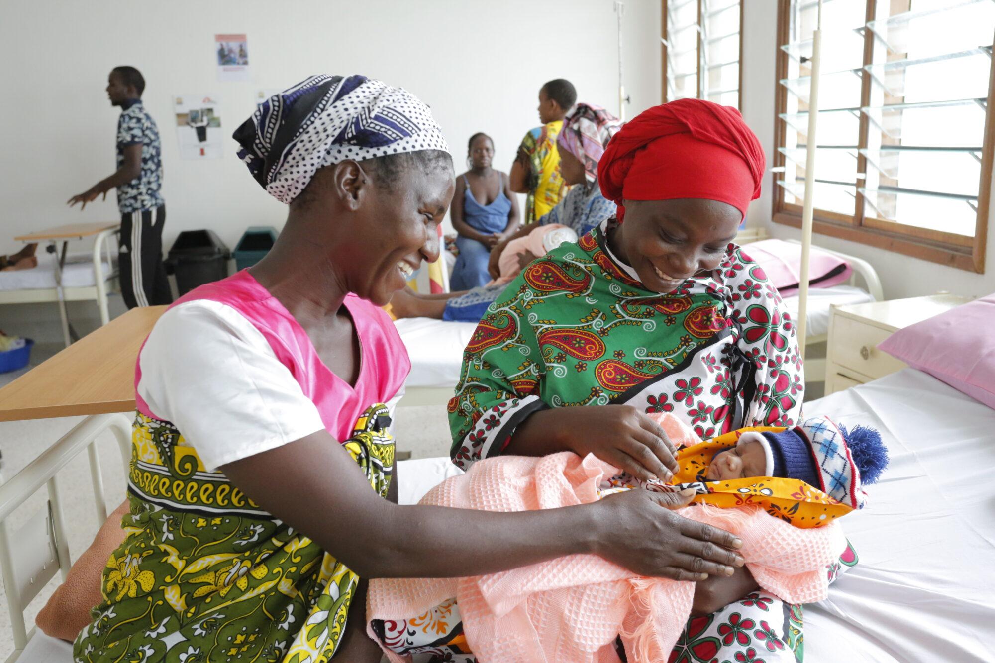 Kaksi naista istuu sairaalan pedillä, ja toisella on vastasyntynyt vauva sylissään.