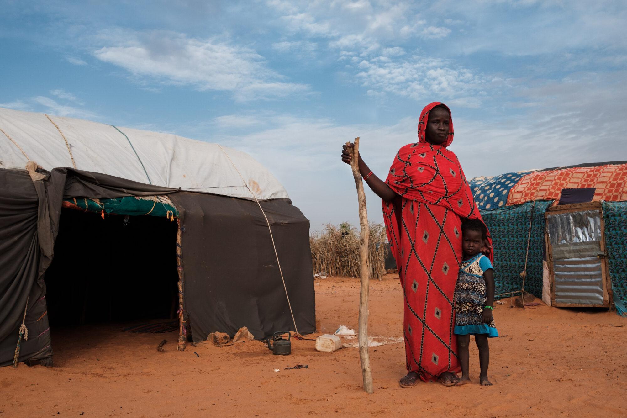 Nainen ja lapsi seisovat kotinsa edessä pakolaisleirillä.