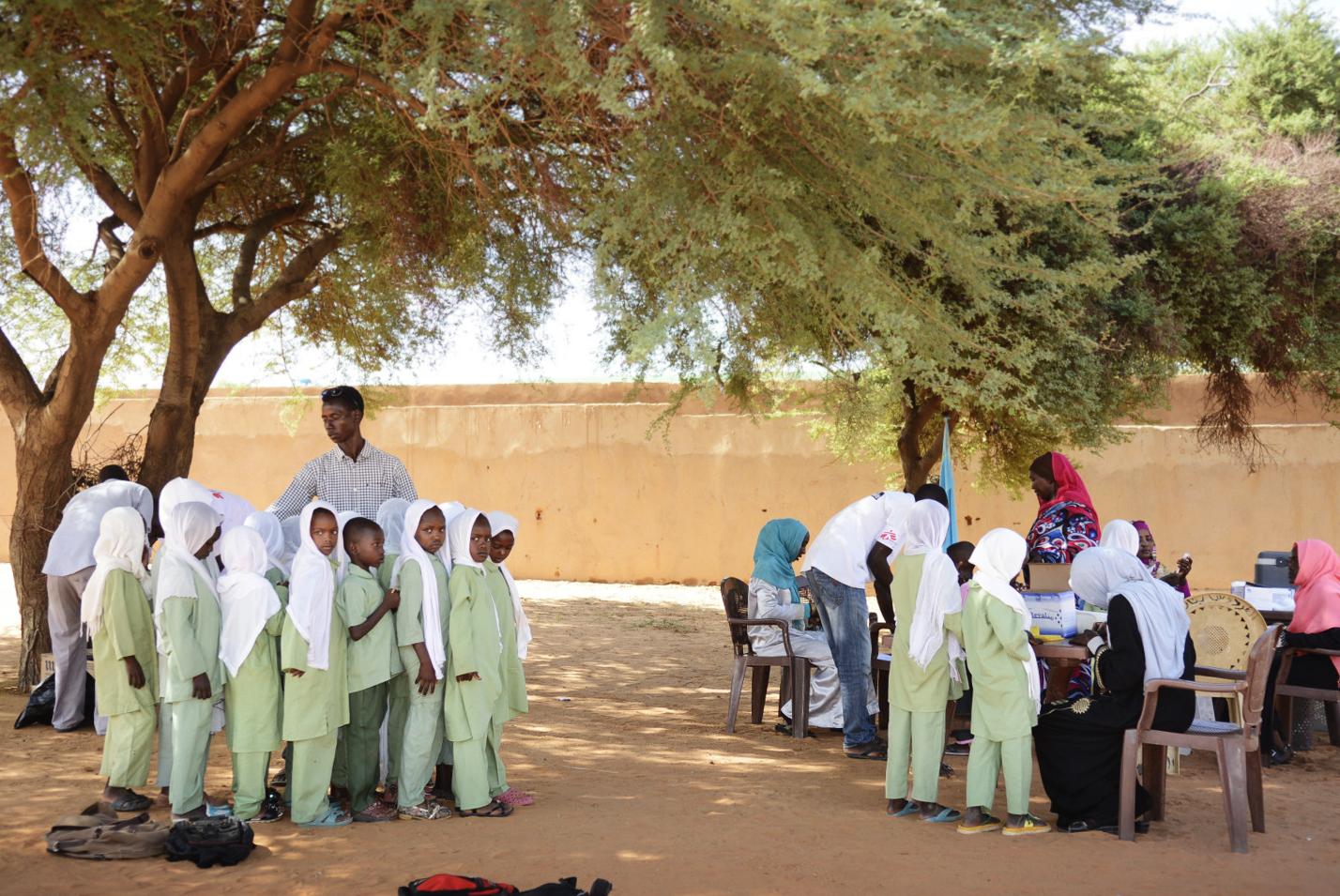 Koulun oppilaat jonottavat rokotusta koulupuvuissaan.
