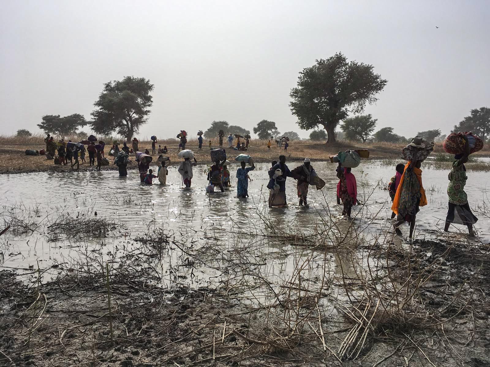 Ihmiset pakenevat joen yli, kun Rann-kylään hyökättiin.