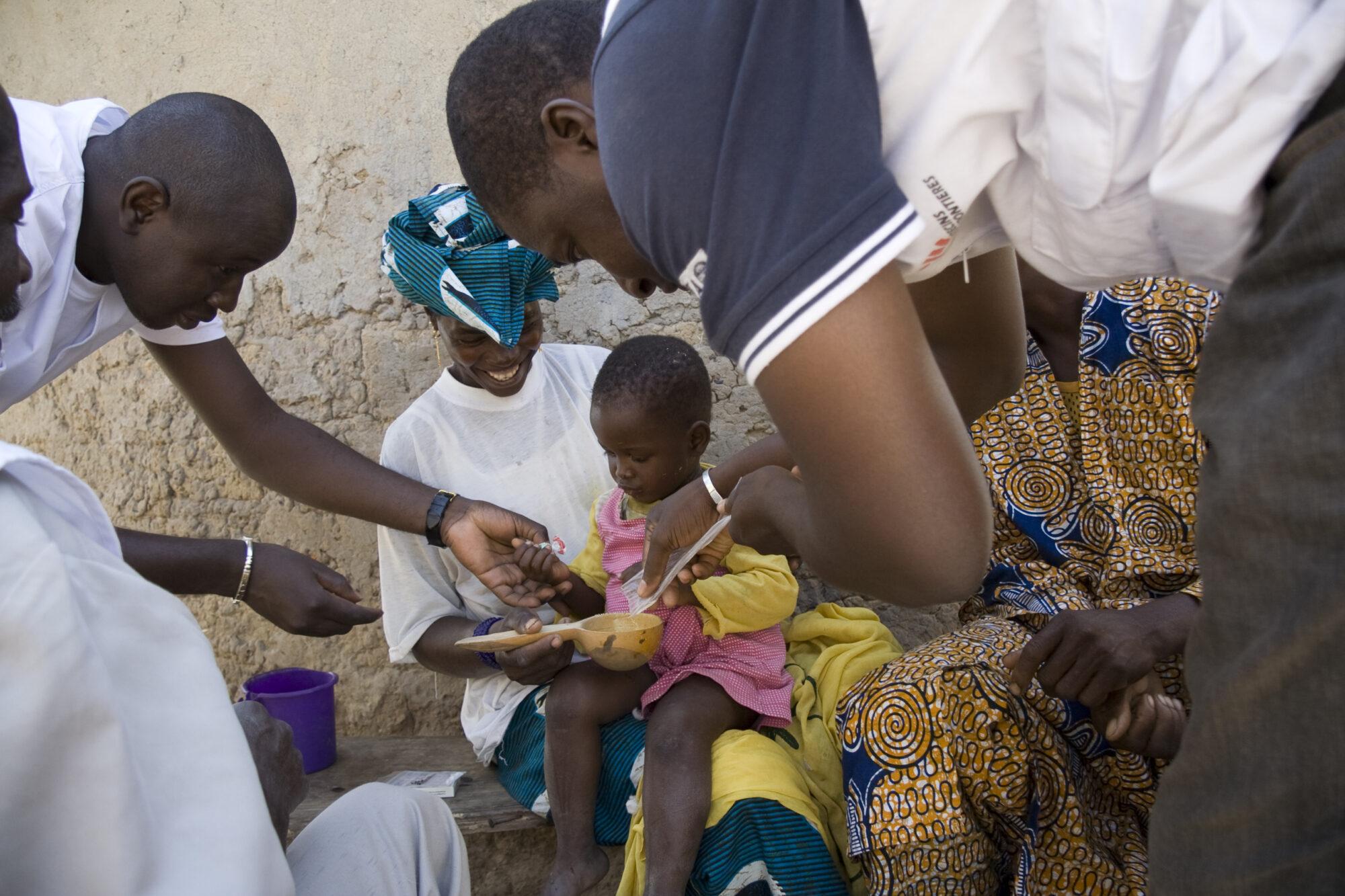 Äiti ja kaksi työntekijää auttavat pientä lasta ottamaan malarialääkkeen.