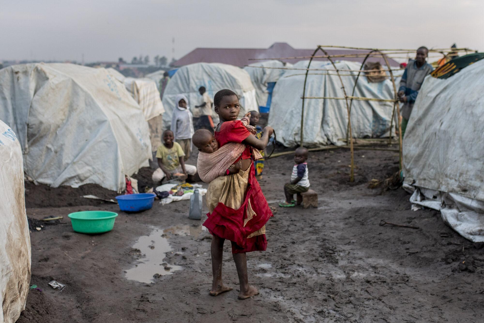 Tyttö kantaa sisartaan pakolaisleirillä Buniassa.