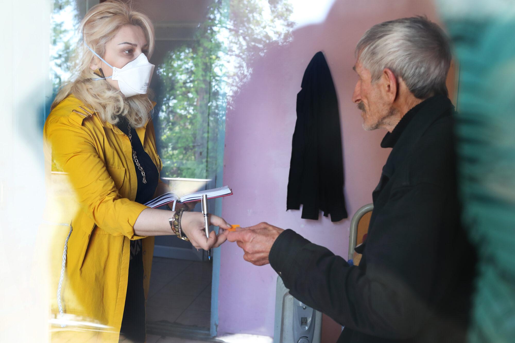 Työntekijä antaa tuberkuloosipotilaalle paperilappua.