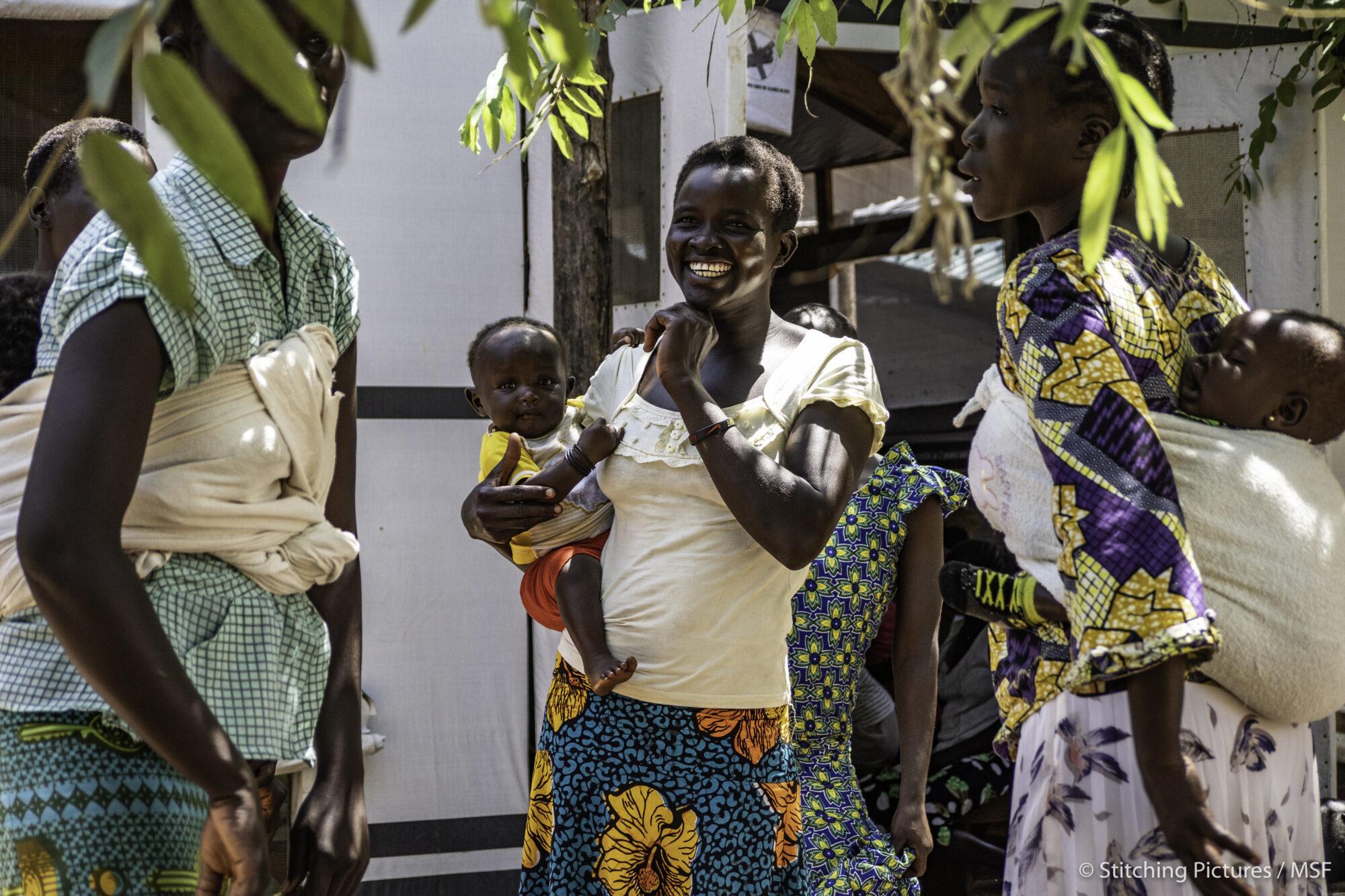 Naiset keskustelevat ja nauravat poliklinikalla pakolaisleirillä.