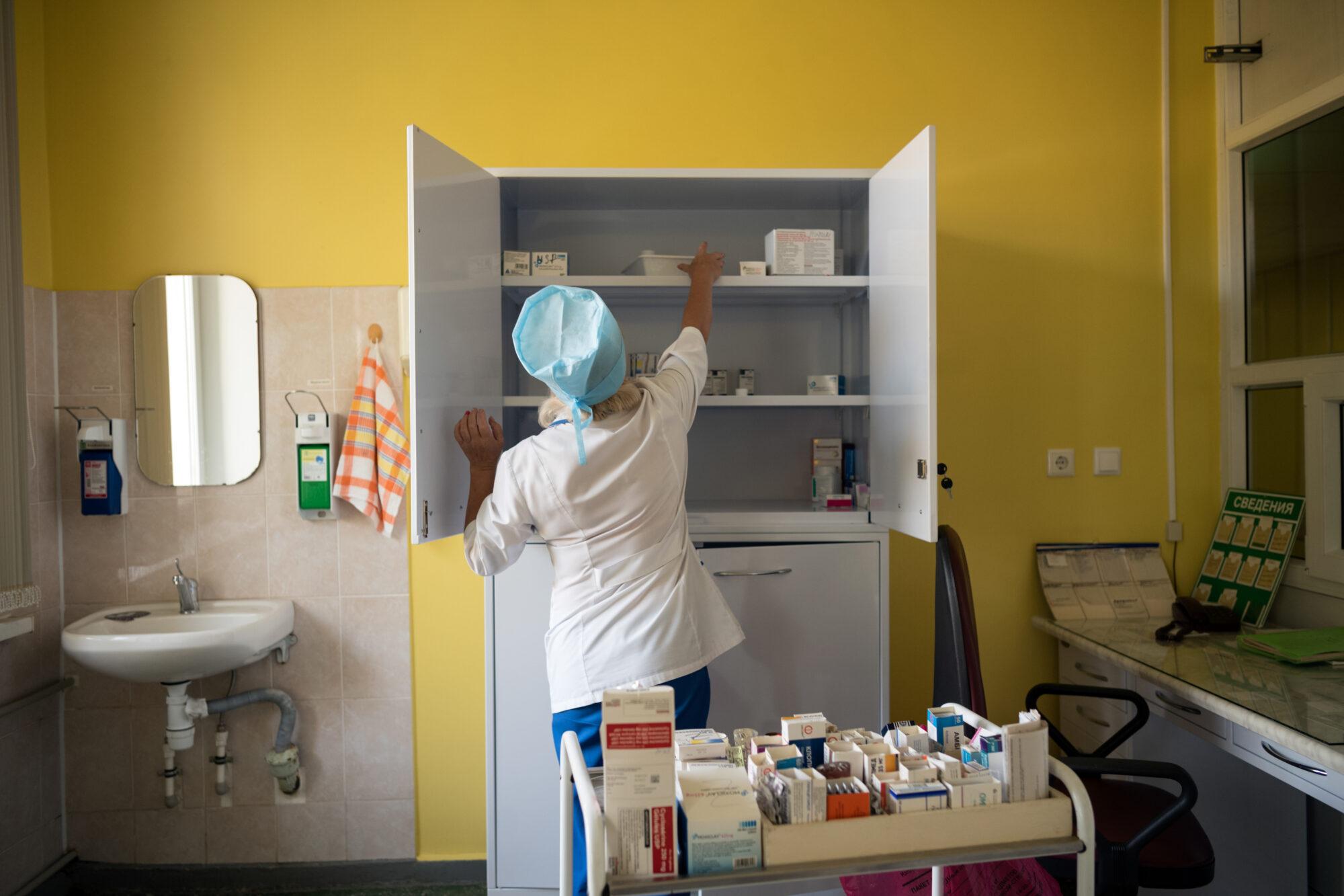 Hoitaja etsii kaapista lääkkeitä valmistellakseen ne tuberkuloosipotilaille.