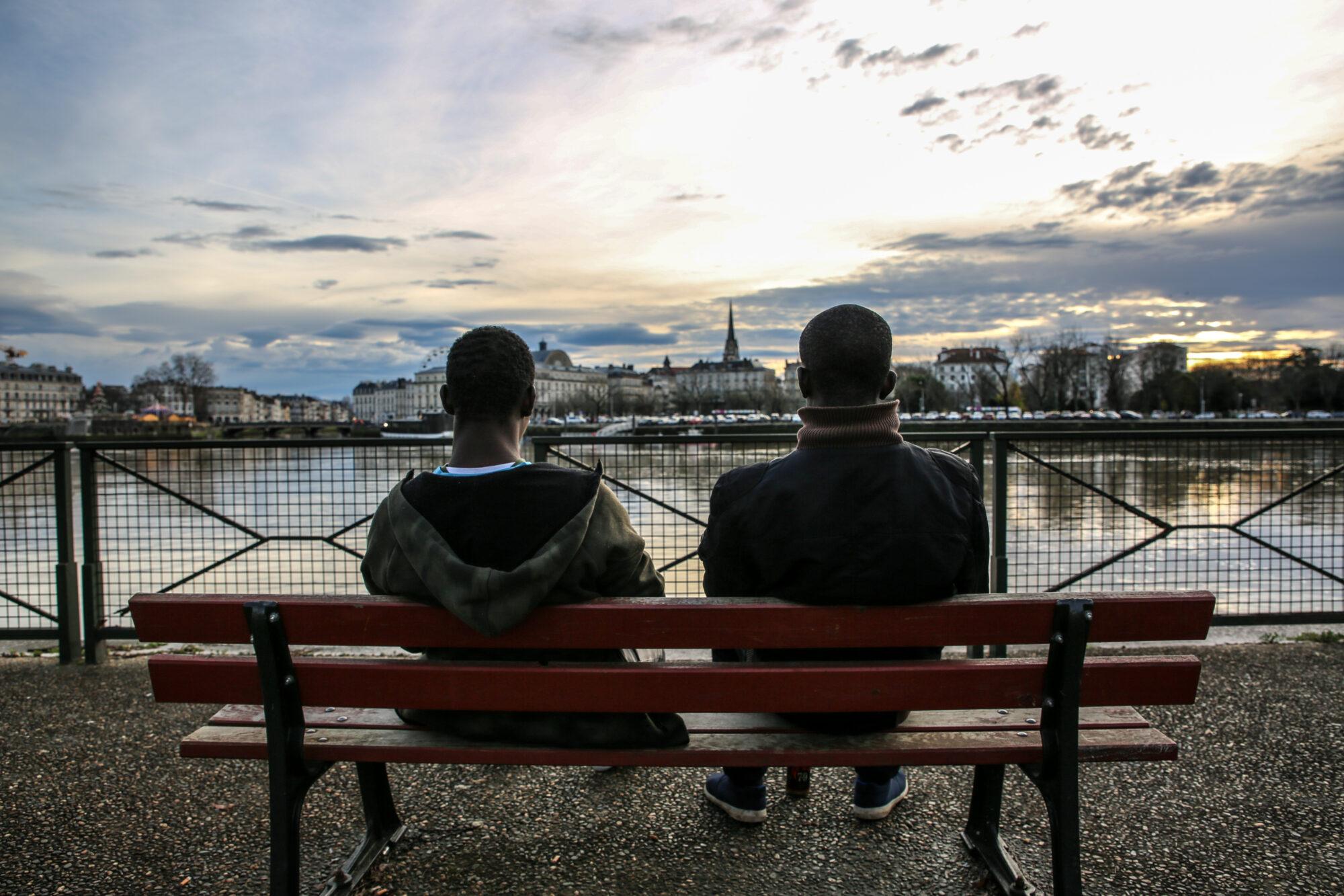 Kaksi siirtolaista istuu penkillä katsellen Adour-jokea Ranskassa.
