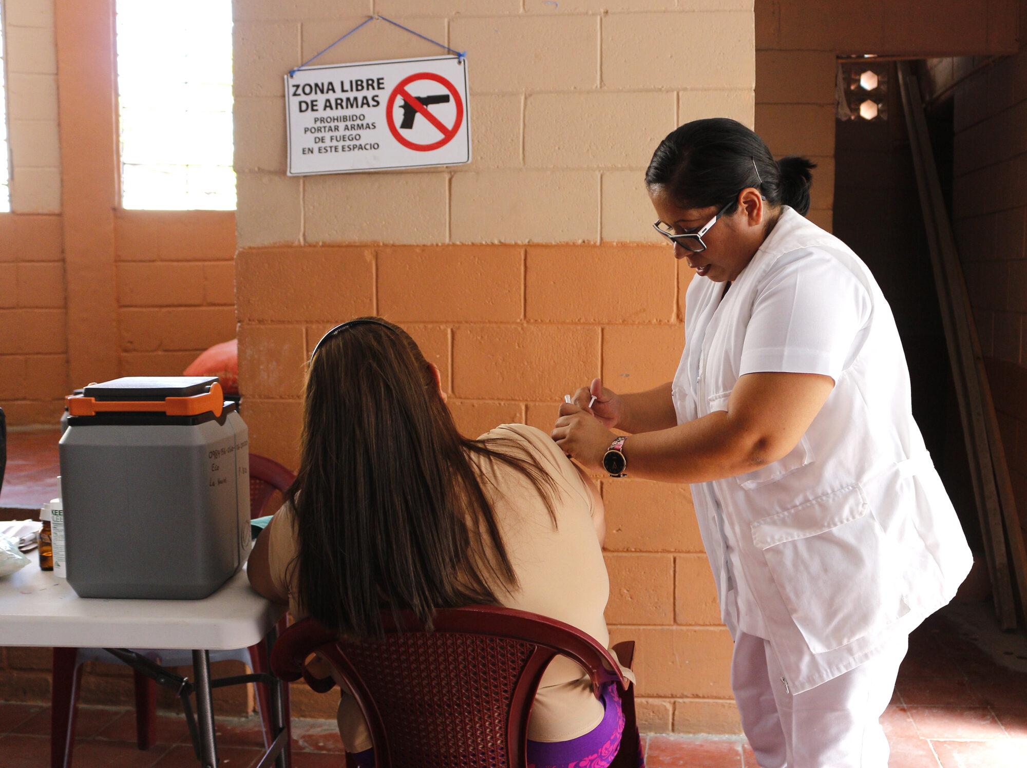 """Työntekijä rokottaa potilasta kyltin alla, jossa lukee """"aseista vapaa alue""""."""