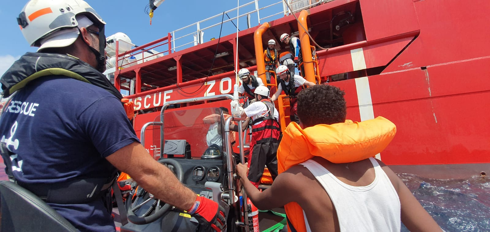 Merihädästä pelastettuja ihmisiä autetaan laivaan tikkaita pitkin, yksi kerrallaan.
