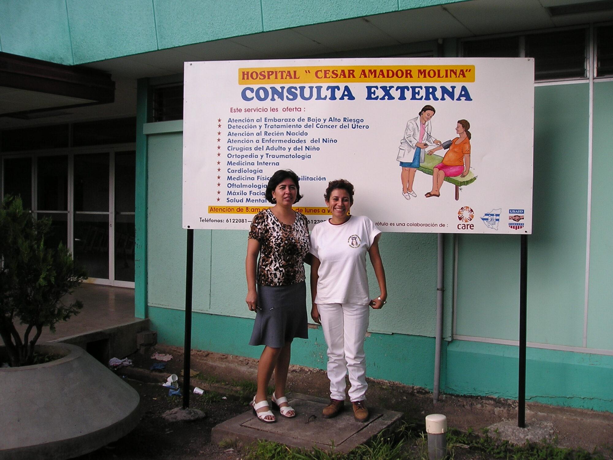 Kaksi työntekijää seisoo sairaalarakennuksen edessä.