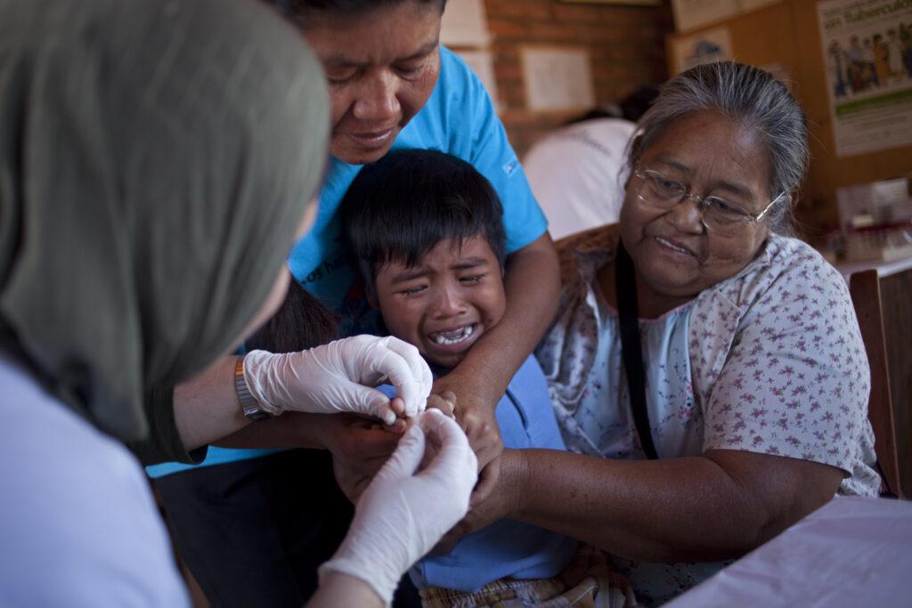 Perheenjäsenet pitävät kiinni itkevästä lapsesta, jonka sormesta otetaan verinäytettä.