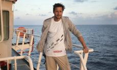 Kuva lyhythiuksisesta miehestä, jolla on valkoinen paita ja harmaa hammari. Mies on laivan kannella.