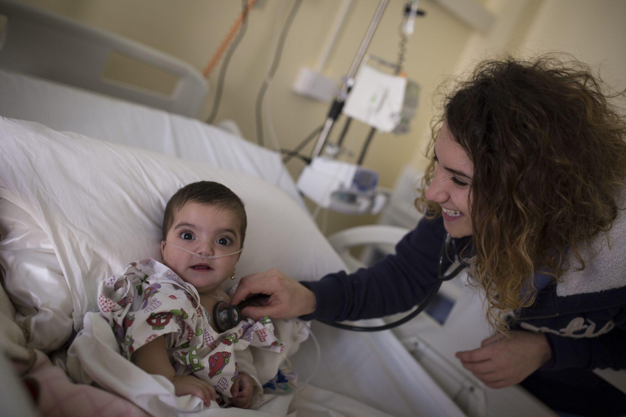Hymyilevä nainen kuuntelee stetoskoopilla vauvan keuhkoja.