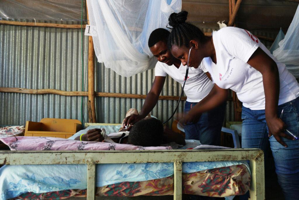 Kaksi lääkäriä kumartuneena sängyssä makaavan potilaan ylle. Toinen lääkäreistä kuuntelee stetoskoopilla potilaan keuhkoja.