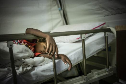 Lapsi makaa sairaalasängyssä.