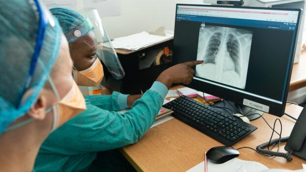 Kaksi lääkäriä tutkii potilaan keuhkokuvia.