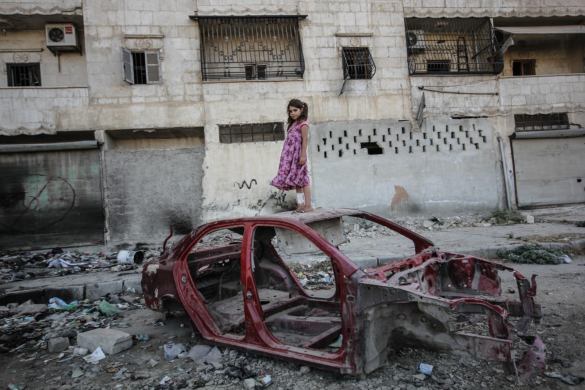 Pieni tyttö seisoo palaneen auton rungon päällä. Hänellä on päällään mekko, ja säären ympärille on kääritty sideharsoa.