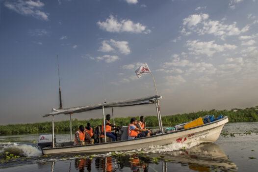Vene kulkee joella. Sen kyydissä on ihmisiä ja kyljessä Lääkärit Ilman Rajoja -järjestön logo.