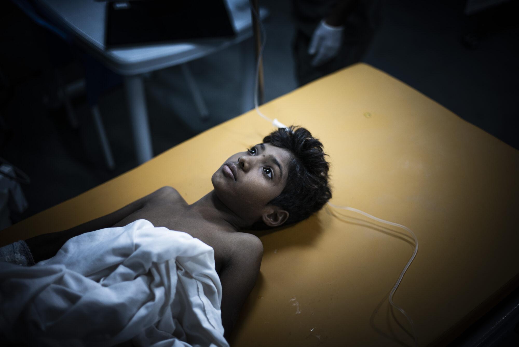 Teini-ikäinen poika makaa sairaalasängyssä.