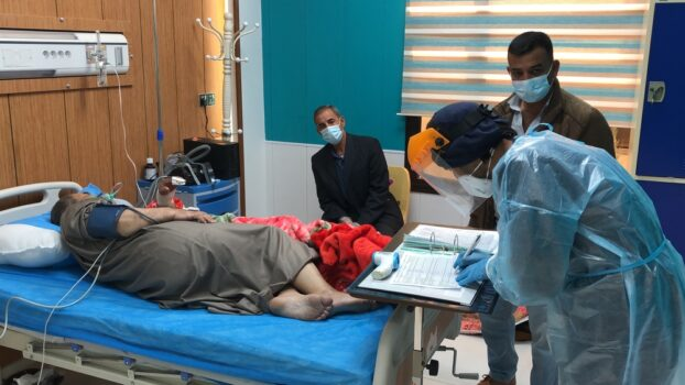 Sairaanhoitaja kirjoittaa muistiinpanoja potilaan sängyn vieressä olevaan kansioon. Potilas makaa sairaalasängyssä ja hänellä on happimaski. Vieressä kaksi muuta miestä, joilla on kasvomaskit.
