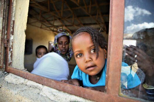 Pieni lapsi nojautuu auki olevalle ikkunalle. Hän katsoo suoraan kameraan.