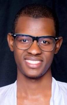 Kuva hymyilevästä miehestä, jolla on valkoinen takki ja silmälasit.